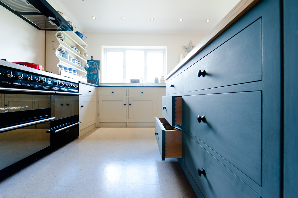 A white painted bespoke timber kitchen with a grey timber island finished with a white worktop